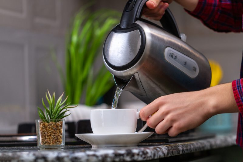 Kobieta zalewa herbatę wodą z czajnika elektrycznego